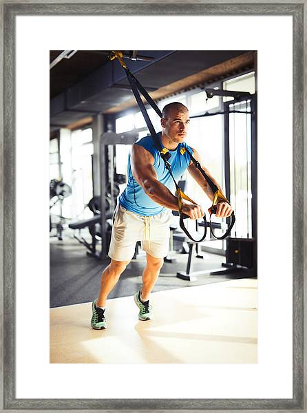 Man Doing Arm Exercises With Suspension Straps At Gym. Framed Print by Emir Memedovski