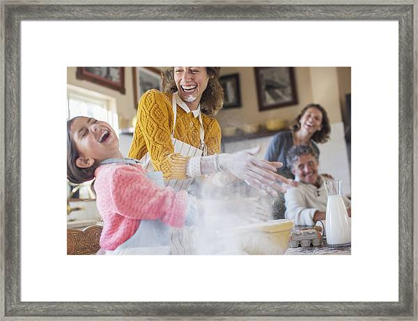 Mother And Daughter Playing With Flour In The Kitchen Framed Print by Caiaimage/Sam Edwards