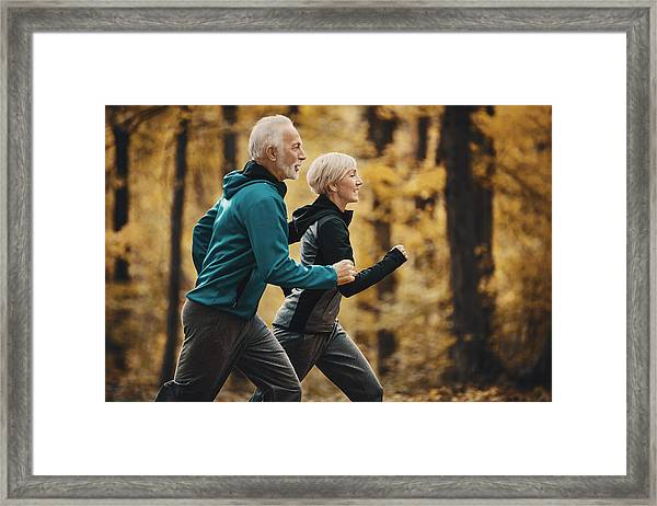 Senior Couple Jogging In A Forest. Framed Print by Gilaxia