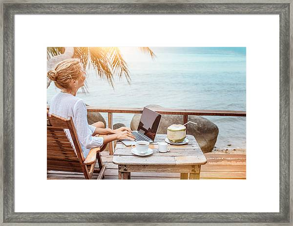 Young Woman Working On Laptop With Coffee And Young Coconut Framed Print by Jasmina007