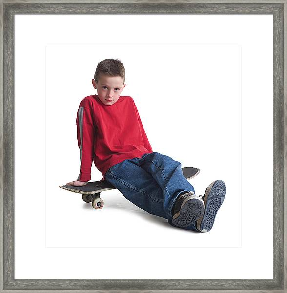A Caucasian Boy In Jeans And A Red Sweater Sits On His Skateboard And Smiles Slightly Framed Print by Photodisc