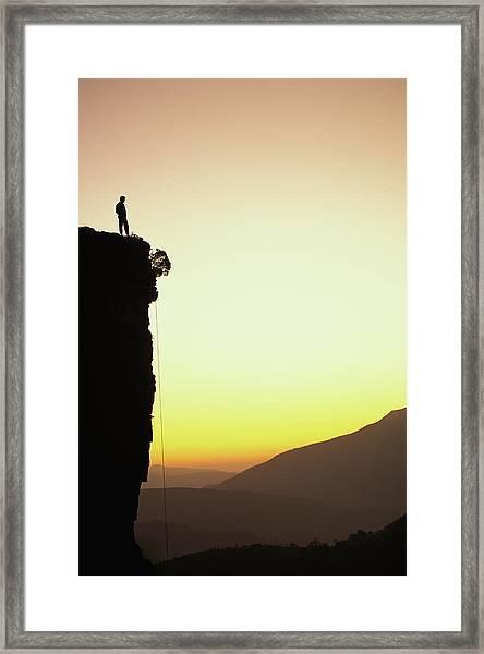 A Climber Stands Atop A Cliff Framed Print