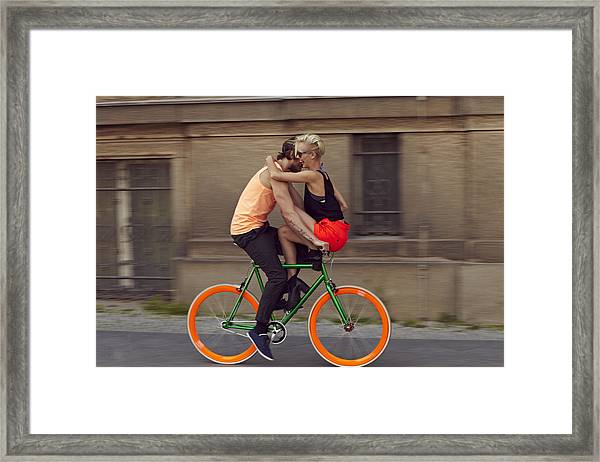 A Couple Biking Through The City Framed Print by Justin Case