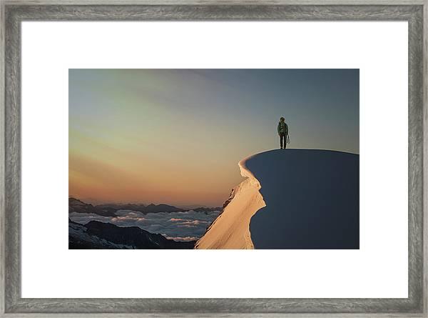A Female Climber On A Snowy Mountaintop Framed Print