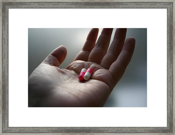 A Hand Holding Two Pills Framed Print by Red Sky