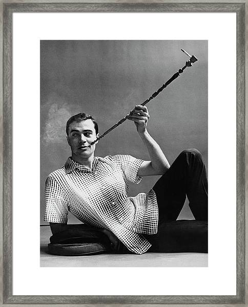 A Male Model Smoking A Cigarette From A Long Pipe Framed Print