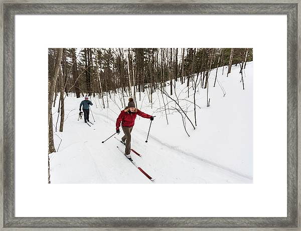 A Man And Woman Cross Country Skiing Framed Print