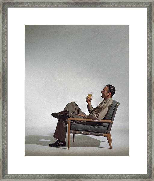 A Man Sitting In An Armchair With A Drink Framed Print