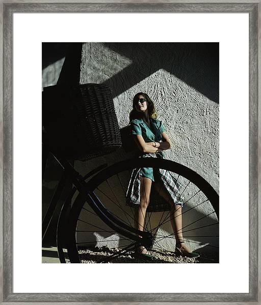 A Model Behind A Bicycle Framed Print by John Rawlings