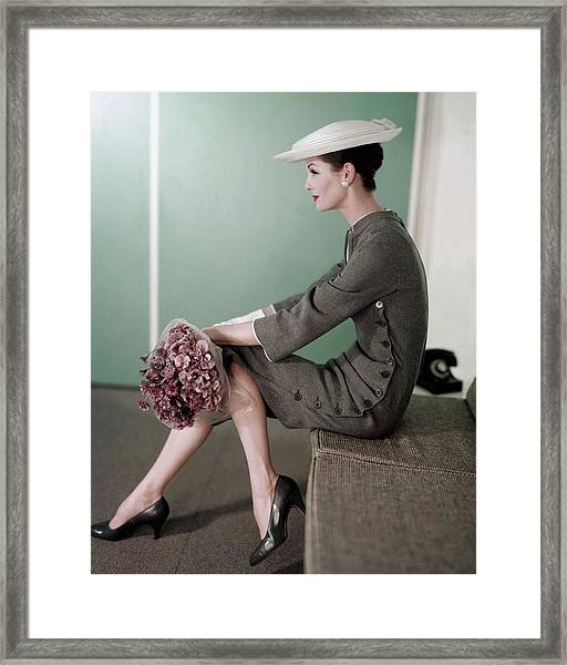 A Model Sitting Down With A Bouquet Of Flowers Framed Print