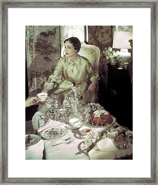 A Model Sitting In A Lavish Dining Room Framed Print