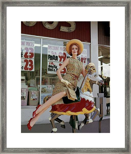 A Model Sitting On A Rocking Horse Framed Print