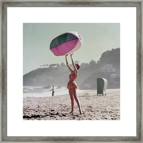 A Model Wearing A Bathing Suit Holding Up An Framed Print by Richard Rutledge
