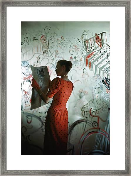 A Model Wearing A Polka Dot Dress Reading Framed Print by Constantin Joffe