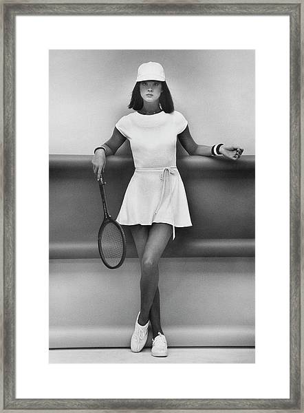 A Model Wearing A Wrap Dress And Cap Framed Print