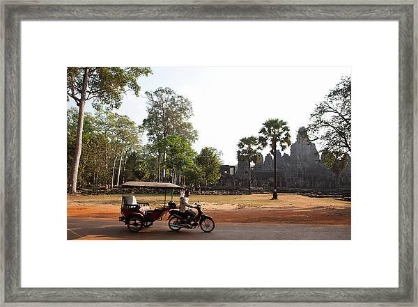 A Tuk Tuk Drives Past The Bayon In Siem Framed Print