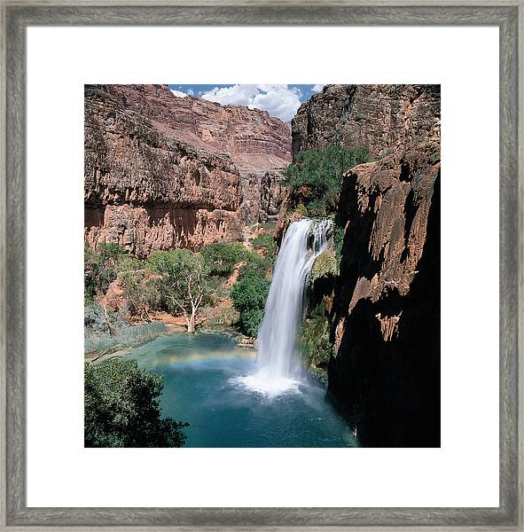 A Waterfall Falls Into Blue-green Water Amongst Green Trees And Jagged Mountain Cliffs Under A Blue Sky With Clouds Framed Print by Photodisc