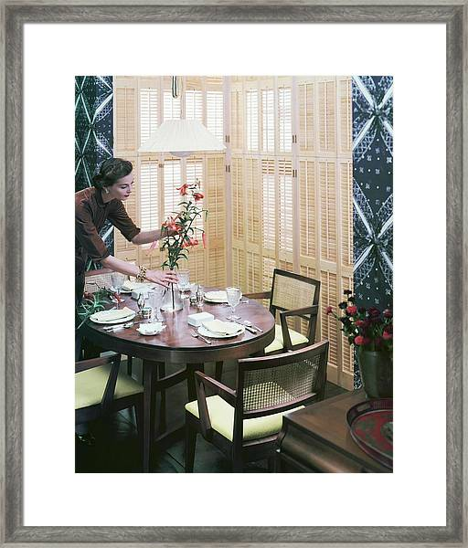 A Woman Arranging Flowers On A Dining Table Framed Print