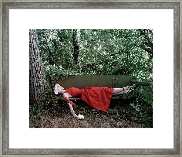 A Woman Lying On A Bench Framed Print by John Rawlings