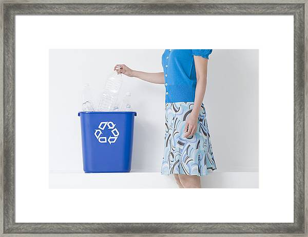 A Woman Putting A Bottle In A Recycling Bin Framed Print by Image Source