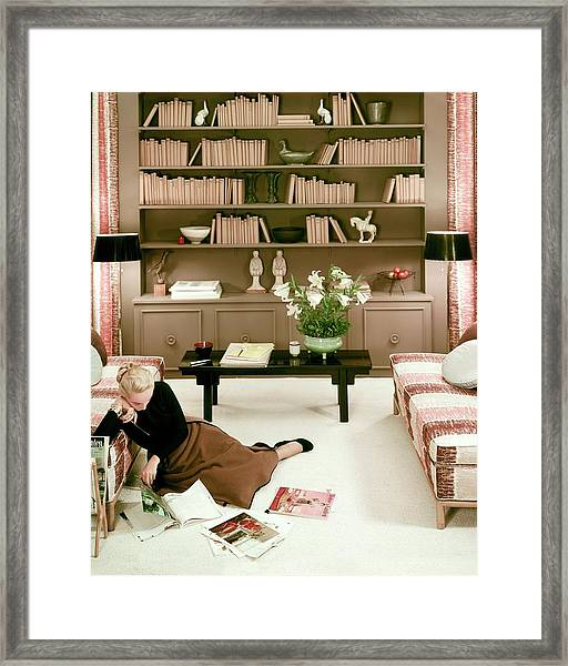 A Woman Reading Magazines On The Floor Framed Print
