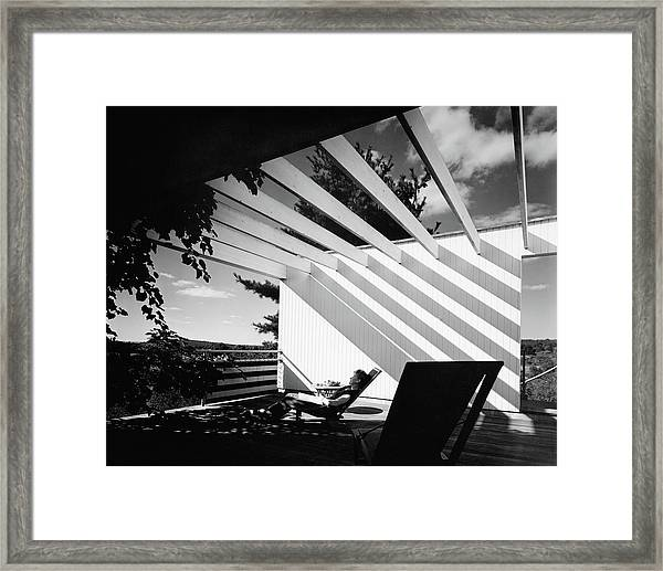 A Woman Sitting On A Reclining Chair On A Rooftop Framed Print