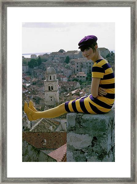 A Woman Sitting On A Stone Wall Framed Print