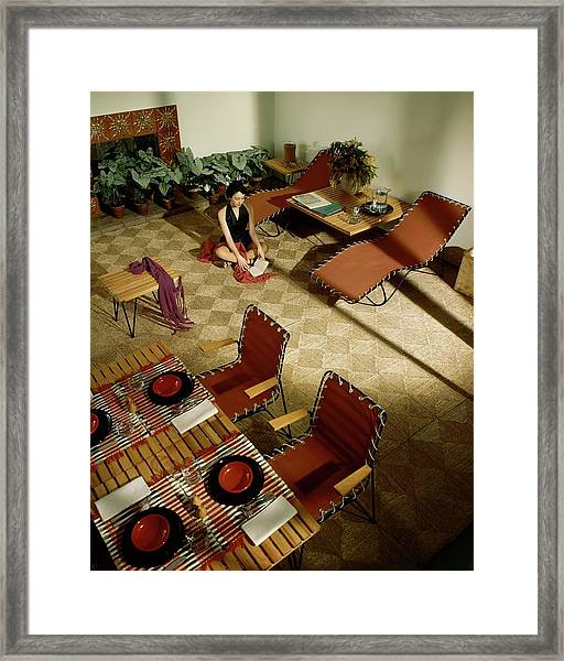 A Woman Sitting On The Floor Of Her Living Room Framed Print by Herbert Matter