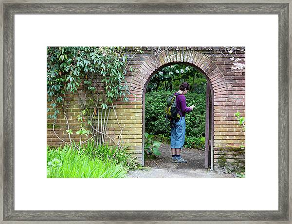 A Woman Standing Under An Archway Framed Print