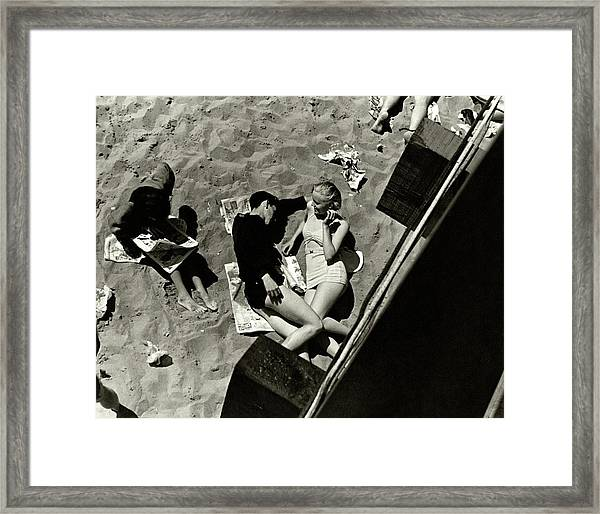 A Young Couple Lying On A Beach Framed Print