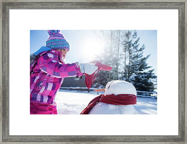 A Young Girl Building A Snowman Framed Print