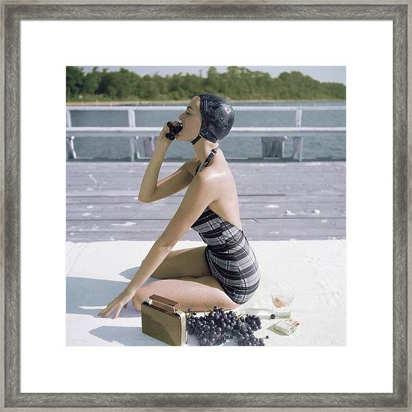 A Young Woman Wearing A Swimsuit Eating Grapes Framed Print
