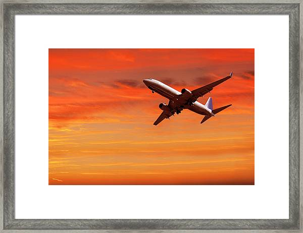 Airplane Flying In Red Sky At Sunset Framed Print