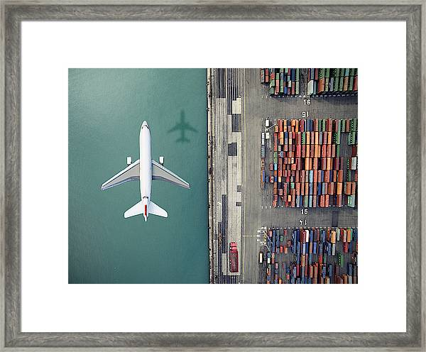 Airplane Flying Over Container Port Framed Print by Orbon Alija