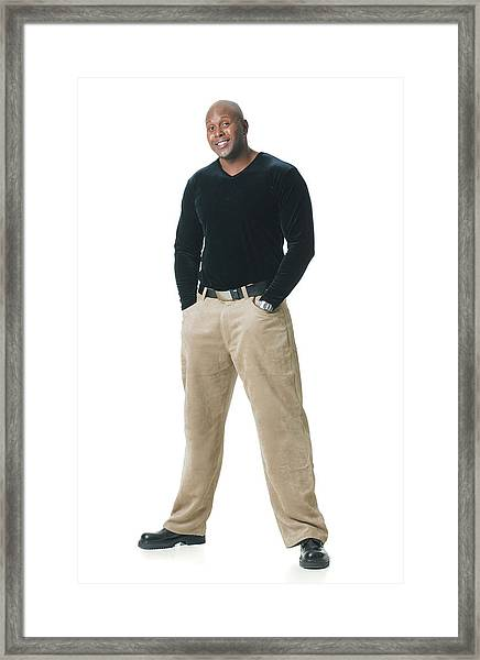 An African American Man In Tan Pants And A Black Shirt Puts His Hands In His Pockets And Smiles Framed Print by Photodisc