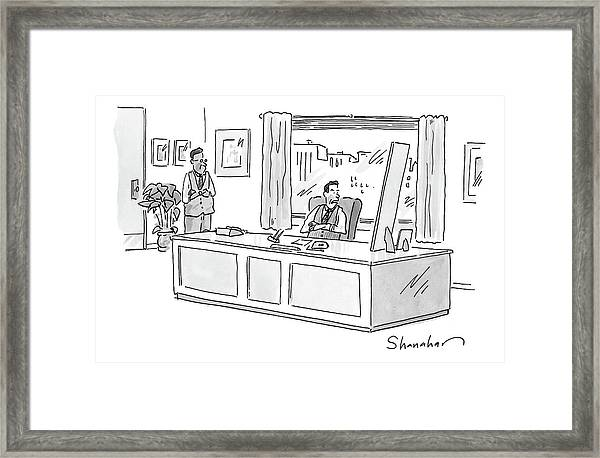 An Executive Looks At Two Pictures On His Desk Framed Print