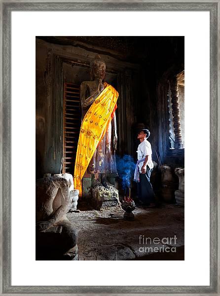 Angkor Wat Devotee Lights Incense In Buddha Temple Framed Print