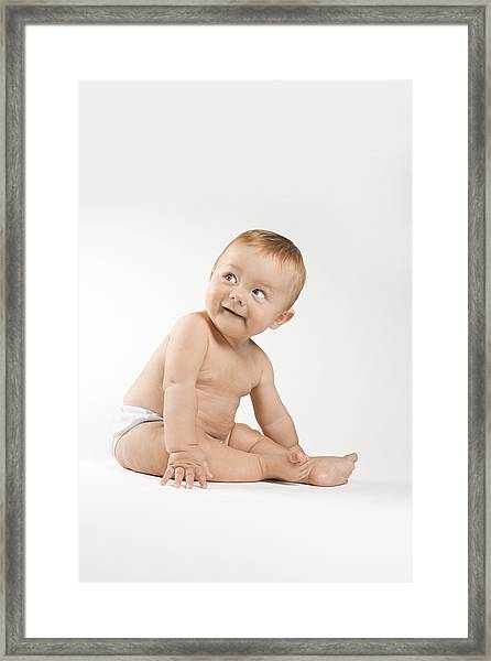 Baby Sitting On Floor Looking Up Framed Print by Jupiterimages