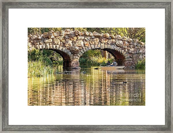 Boaters Under The Bridge Framed Print