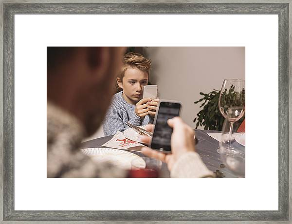 Boy Playing With His Smartphone After Christmas Dinner Framed Print by Westend61