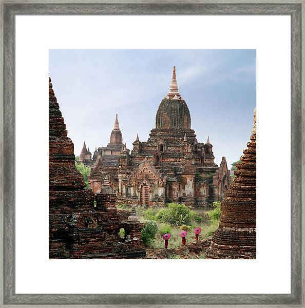 Buddhist Monks Walking Past Temple Framed Print by Martin Puddy