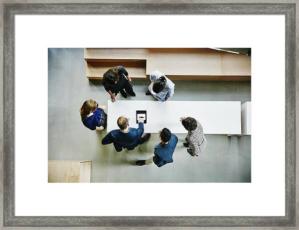 Business Colleagues Discussing Project In Office Framed Print by Thomas Barwick