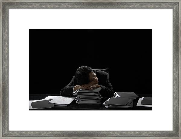 Businessman Asleep At Desk Resting Head On Stack Of Files Framed Print by James Woodson