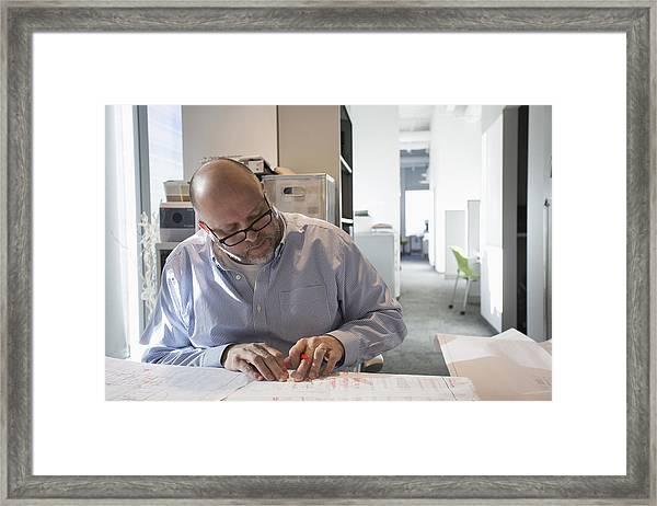 Businessman Sketching Blueprints In Office Framed Print by Hill Street Studios
