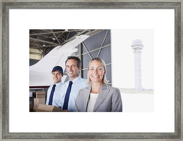 Businesswoman And Workers Standing In Hangar Framed Print by Martin Barraud