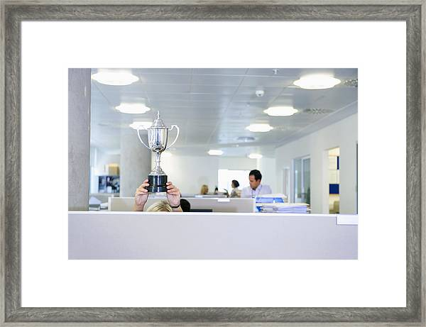 Businesswoman Holding Trophy Over Office Cubicle Framed Print by Jacobs Stock Photography Ltd