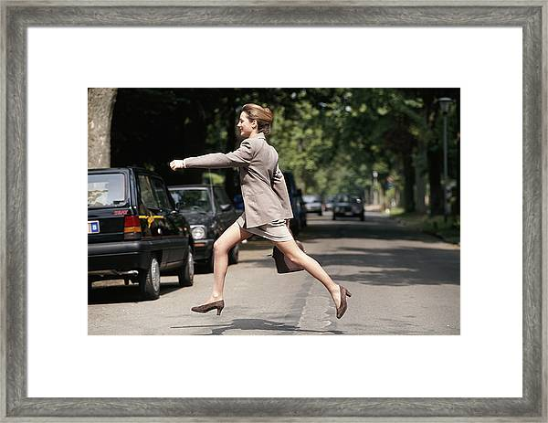 Businesswoman Running Across Road, Side View Framed Print by David De Lossy