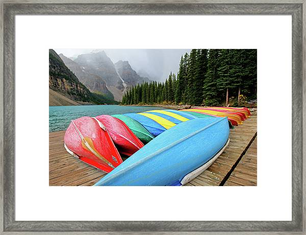 Canoes Line Dock At Moraine Lake, Banff Framed Print by Wildroze