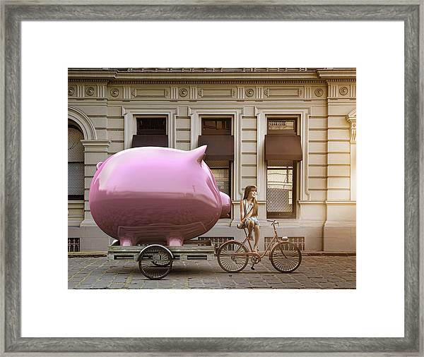 Caucasian Girl Pulling Piggy Bank On Bicycle Cart Framed Print by Colin Anderson Productions pty ltd