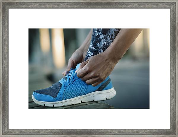 Close-up Of Woman Tying Shoelace On Bench Framed Print by Maskot